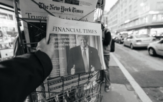 Paris, France - November 10, 2016: Man buying Financial Times press magazine with shocking headline title at press kiosk about the US President Elections - Donald Trump is the 45th President of United States of America